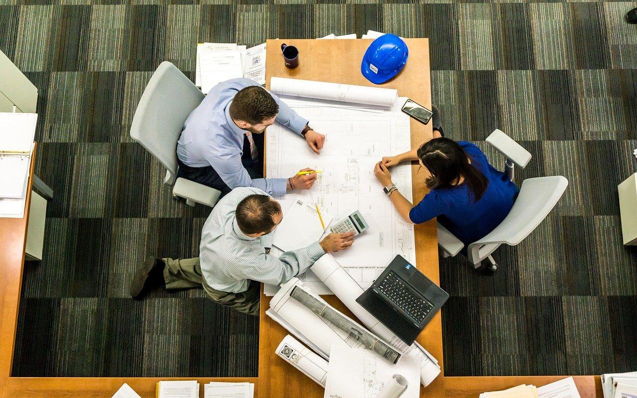trois personnes assies au même bureau pendant une réunion