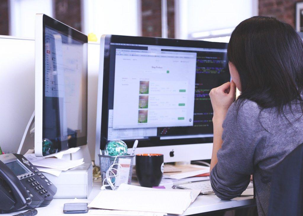 personne qui travaille sur un ordinateur à deux écrans