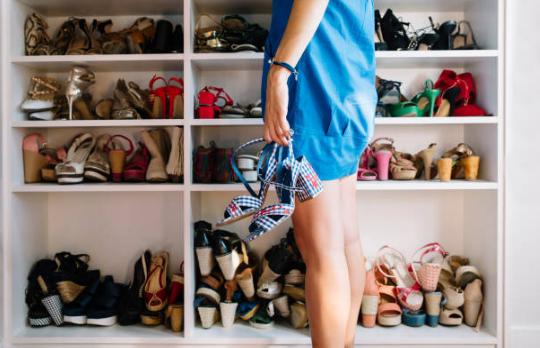 femme se tenant devant un placard rempli de chaussures